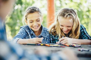 Smiling Caucasian girls coloring outdoors