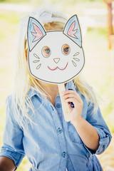 Caucasian girl holding cat mask