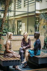 Businesswomen talking in office courtyard