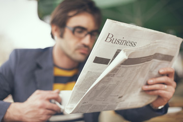 Close up of man reading business section of newspaper