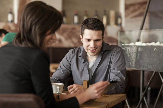 Couple using cell phone in cafe