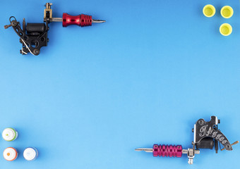 Two tattoo machines with three bottles of ink and three ink containers on blue background. Tattoo guns.