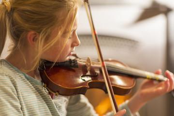 Close up of Caucasian girl practicing violin