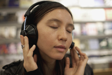 Young woman listening to music in a record store