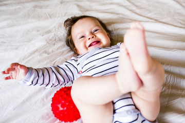 Caucasian baby girl laughing on bed