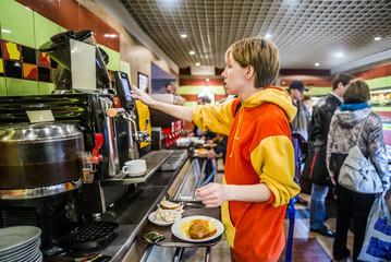 Caucasian woman getting breakfast in cafeteria