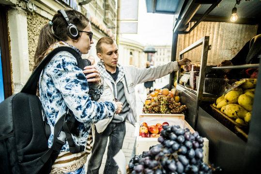 Caucasian couple buying produce at fruit kiosk