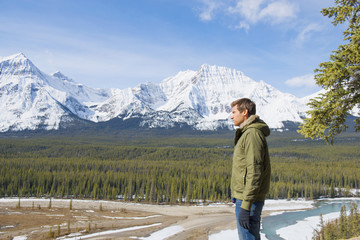 Caucasian man admiring scenic view of forest and mountains, Banff, Alberta, Canada