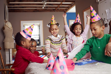 Children wearing party hats and celebrating at table