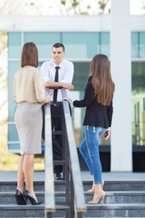 Group of three happy young business people on a coffee break in front of the office building. Front view of young man talking to his coworkers and rear view of two women looking at him.