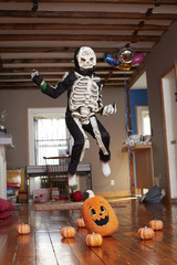 Black boy jumping over pumpkin in skeleton Halloween costume