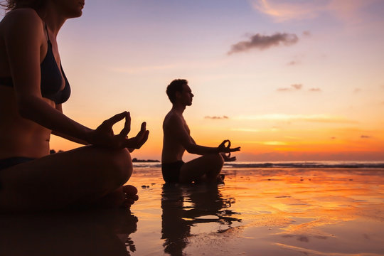 group of people meditating on the beach, yoga and health background