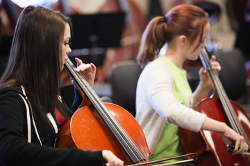 Caucasian students playing cello in high school band class