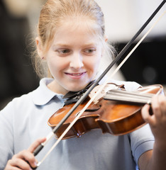 Caucasian student playing violin in middle school band class