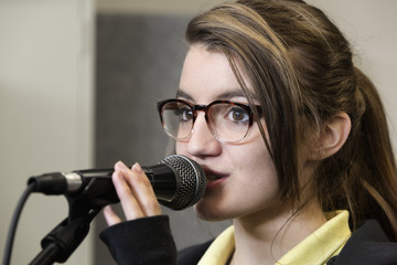 Caucasian student with eyeglasses singing into microphone
