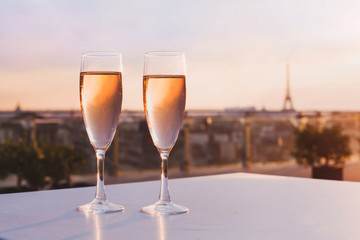 two glasses of champagne at rooftop restaurant with view of Eiffel Tower and Paris skyline, luxury romantic dinner for couple