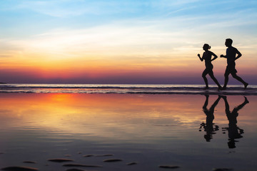 two runners on the beach, silhouette of people jogging at sunset, healthy lifestyle background with copyspace