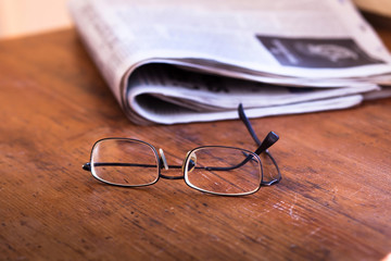 reading newspapers, glasses and daily news on wooden table
