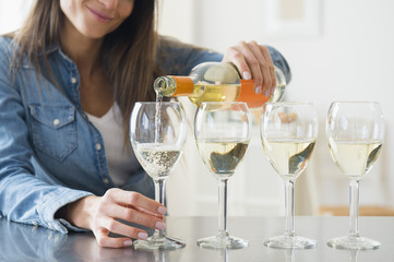 Woman pouring white wine in wine glasses