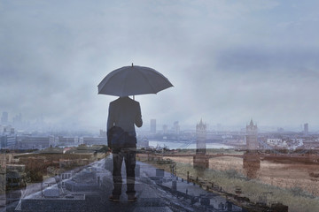 double exposure photo of business man with umbrella and London skyline, panoramic view of the city