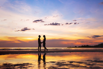 silhouette of afectionate couple on the beach at sunset, love concept, man and woman, beautiful background