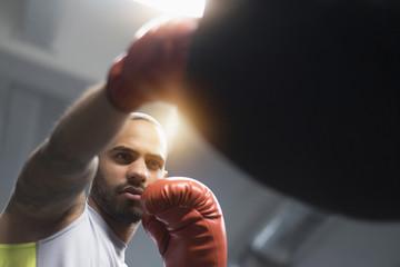 Close up of Hispanic man punching bag in gym