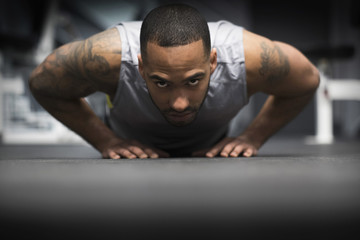 Hispanic man doing push-ups in gym