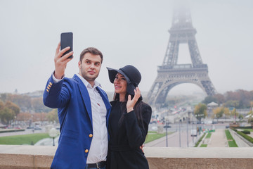 couple of tourists taking photo with Eiffel Tower in Paris, selfie, tourism in Europe, France