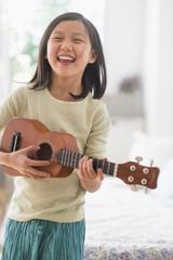Chinese girl practicing ukulele in bedroom