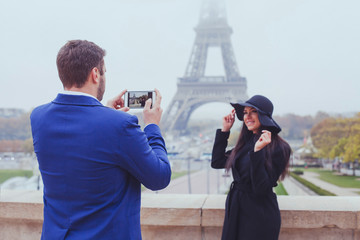 mobile photography, man taking photo of woman with his phone, couple of tourists near Eiffel Tower in Paris, France