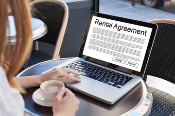 Fototapeta rental agreement, rent a car or house, woman reading tenancy contract on the screen of laptop