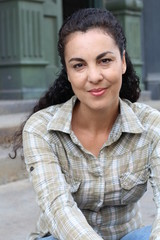 Vertical image of beautiful hispanic woman in a casual plaid shirt in the city