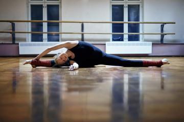 Caucasian dancer stretching doing splits on studio floor