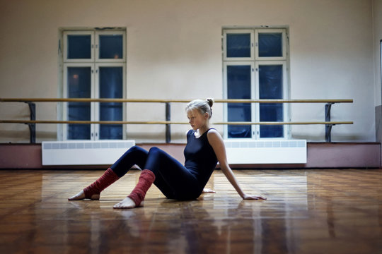 Caucasian dancer sitting on studio floor