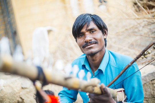 Indian man holding traditional instrument