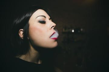 Caucasian woman smoking in nightclub