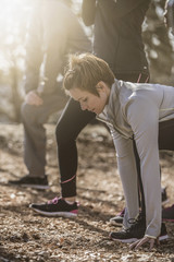 Runners stretching on dirt ground