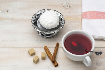 Cup of red tea. Cane sugar and cinnamon sticks with sweet dessert