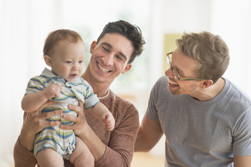 Caucasian gay fathers holding baby