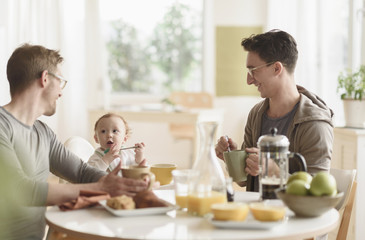Caucasian gay fathers and baby eating breakfast