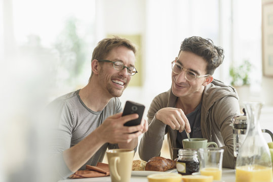Caucasian gay couple using cell phone at breakfast