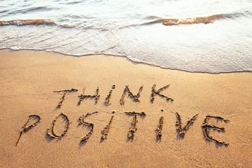think positive, concept written on the sand