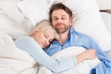 Couple Sleeping Together In Bed
