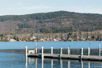 Color DSLR stock image of a frozen Lake George, with metal and wood pier in the foreground and Adirondack Mountains in background. Horizontal with copy space for text