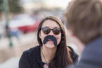 Teenage girl wearing fake mustache