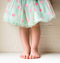 Toddler in green and pink polka dot skirt against white brick wall (cropped)