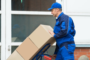 Delivery Man Carrying Boxes On A Hand Truck