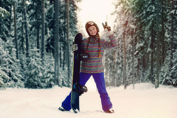 Caucasian snowboarder making peace sign in snowy forest