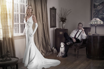 Caucasian bride and groom in study with dogs