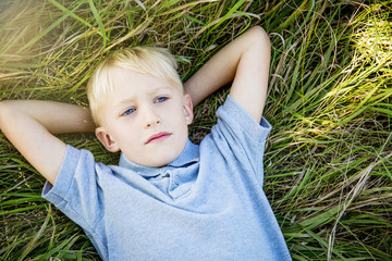 Thoughtful boy lying on the grass